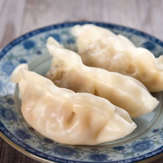 Three steamed vegetable dumplings on pretty blue plate.