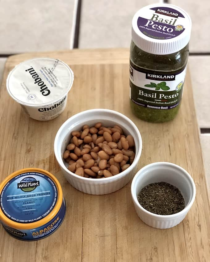 Ingredients for making Summer Tuna White Bean Salad including nonfat Greek yogurt, basil pesto, cooked white beans, canned tuna and Herbs de Provence.
