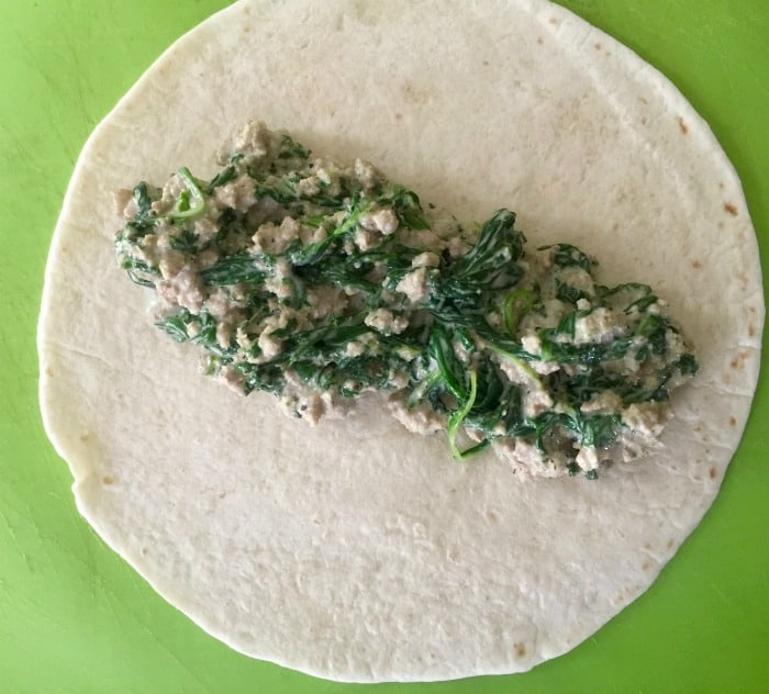 Filling tortilla with turkey, spinach and goat cheese for making enchiladas.