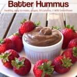 Chocolate brownie batter dessert hummus in white ramekin on white plate with fresh strawberries.