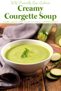 Creamy courgette soup in a white bowl with whole zucchini and zucchini slices scattered about.