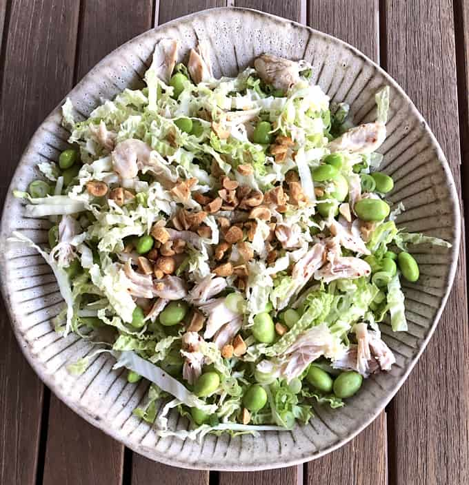 Edamame chicken salad topped with chopped peanuts in ceramic plate on wooden table.