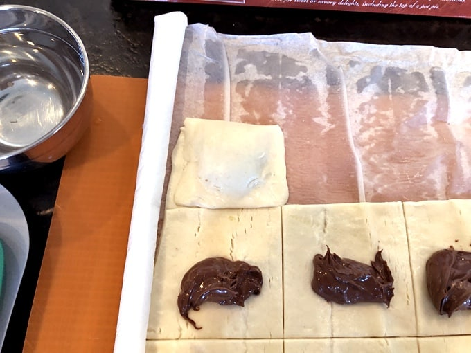 Puff pastry sheet cut into squares and filled with Nutella on parchment paper.