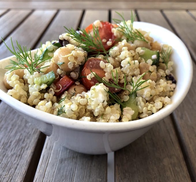 Vegetarian Greek Quinoa Salad garnished with fresh dill in white bowl on wood table.