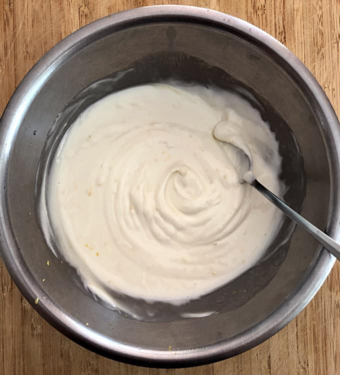 Mixing non-fat Greek yogurt, agave nectar, lemon zest and lemon juice in stainless mixing bowl with spoon.
