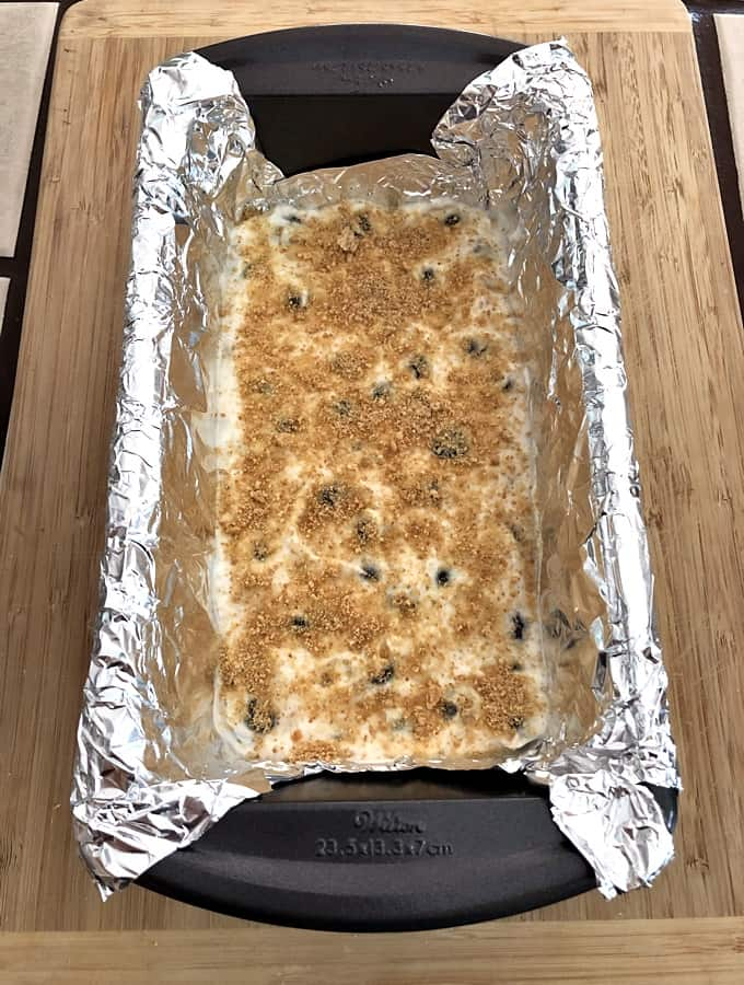 Graham cracker crumbs on cheesecake yogurt mixture in loaf pan.