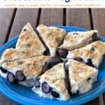 Lemon-Blueberry Cheesecake Yogurt Bark triangles on blue plate on wooden table.