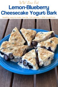 Lemon-Blueberry Cheesecake Yogurt Bark triangles on blue plate on wooden table.