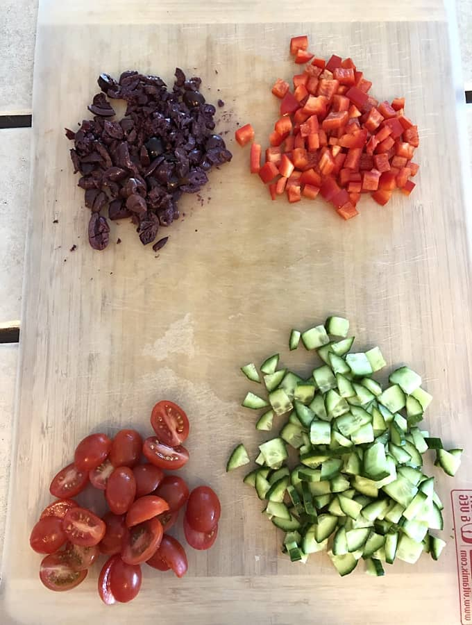 Chopped Kalamata olives, chopped red bell pepper, halved cherry tomatoes and chopped cucumber on cutting board.