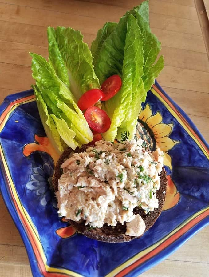 Open-faced salmon salad sandwich with lettuce and tomatoes on whole grain toast on blue ceramic plate.