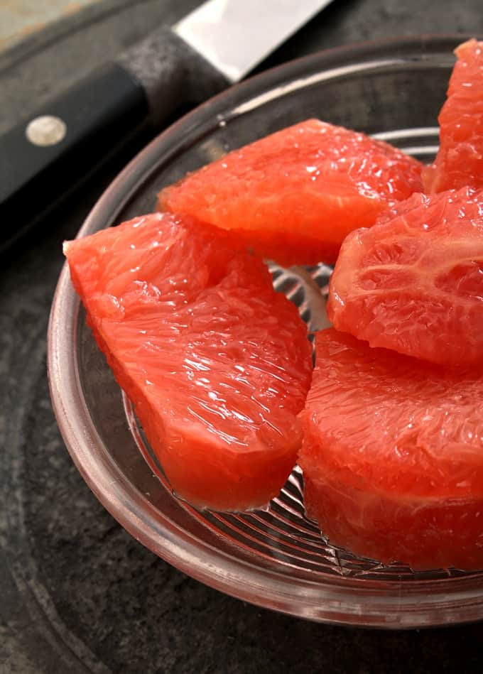 Red grapefruit segments in small glass bowl.