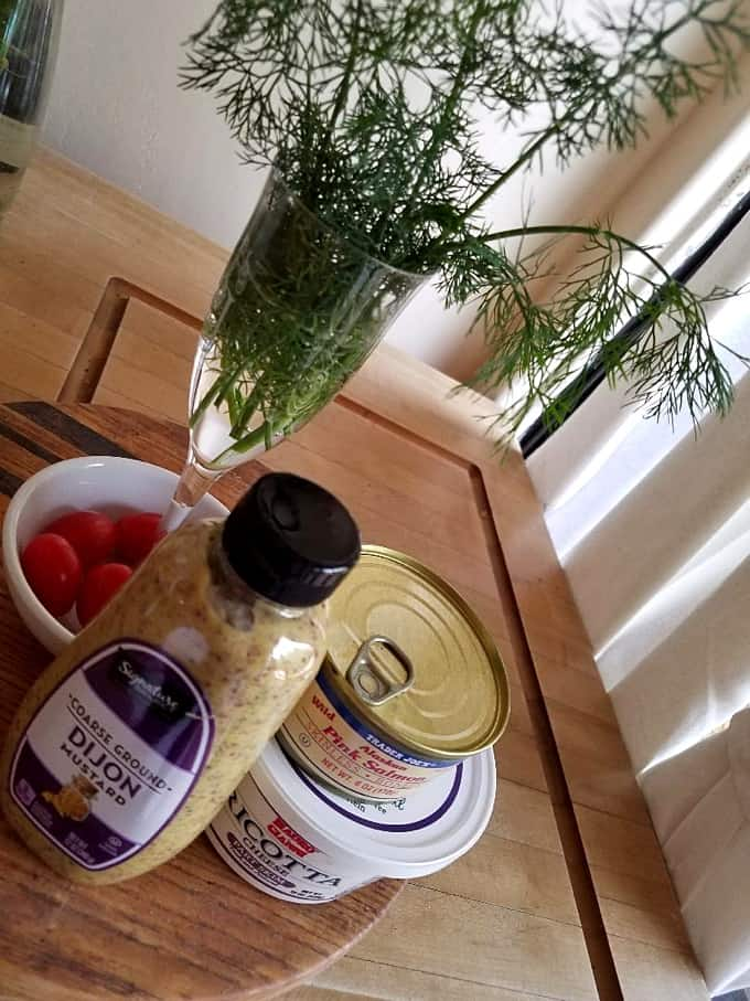Dijon mustard, cherry tomatoes, fresh dill, canned salmon and ricotta cheese for making salmon sandwiches.