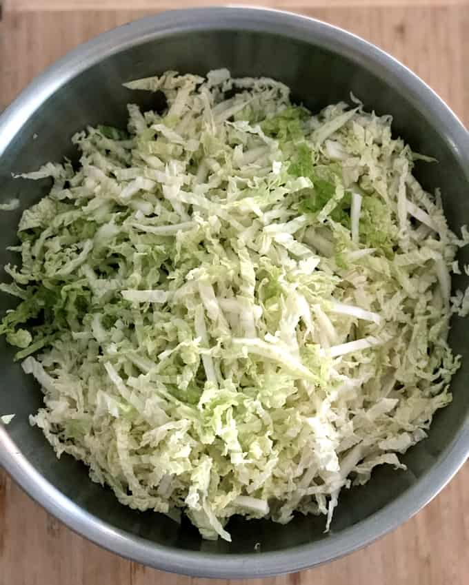 Shredded Napa cabbage in stainless steel bowl on wood cutting board.