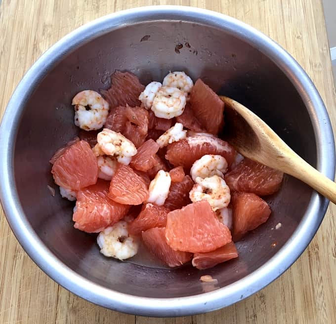 Mixing shrimp, grapefruit and salad dressing in bowl with wooden spoon.