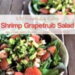 Two shrimp and grapefruit mixed greens salads on ceramic plates on wooden table.