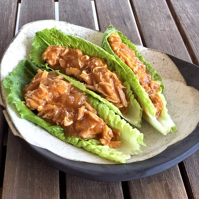 Slow cooker honey sriracha chicken lettuce wraps on ceramic plate on wooden table.