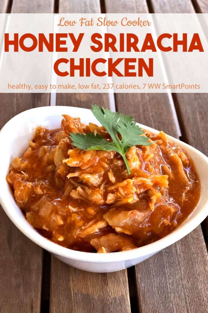 Low fat honey sriracha shredded chicken in a white bowl on a wood table.