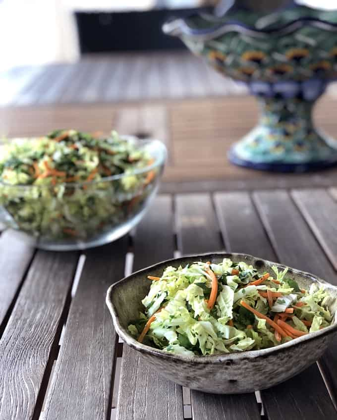 Spicy cabbage slaw in small pottery bowl with large glass slaw bowl in the background near talavera pottery.