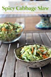 Spicy cabbage slaw in ceramic dish near larger glass bowl with cabbage slaw on wood table.