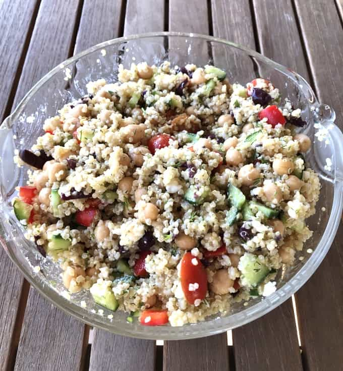 Vegetarian Greek Quinoa Salad in glass bowl on wood table.