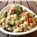 Vegetarian Greek Quinoa Salad in white bowl on wooden table.