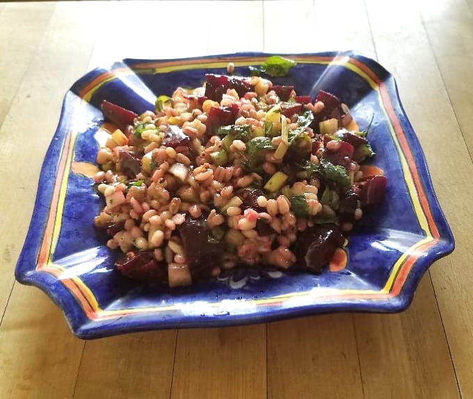 Barley and Beet Salad in blue dish on wood counter.