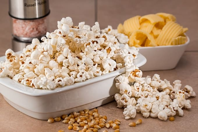 Bowl of popcorn with a bowl of potato chips and extra popcorn scatter on the table.