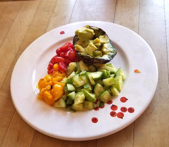 Chopped tomatoes, peppers, Persian cucumbers and avocado on white plate.