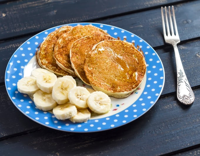 Four banana pancakes with banana slices on plate with fork on blue wood table.