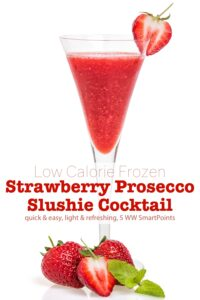 Frozen strawberry prosecco slushie cocktail in champagne flute garnished with fresh strawberries.