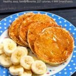 Four banana pancakes with fresh banana slices on blue polka dot plate with a fork.