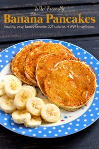 Four banana pancakes with fresh banana slices on blue polka dot plate with a fork.