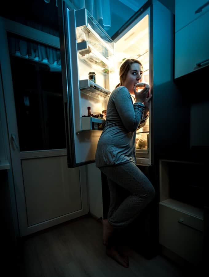 Woman snacking in the refrigerator late at night.