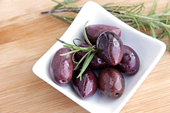 Mediterranean Kalamata olives with fresh rosemary in small white dish.