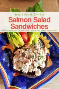 Open-face salmon salad sandwich on whole grain bread with romaine lettuce and cherry tomatoes on blue ceramic plate.