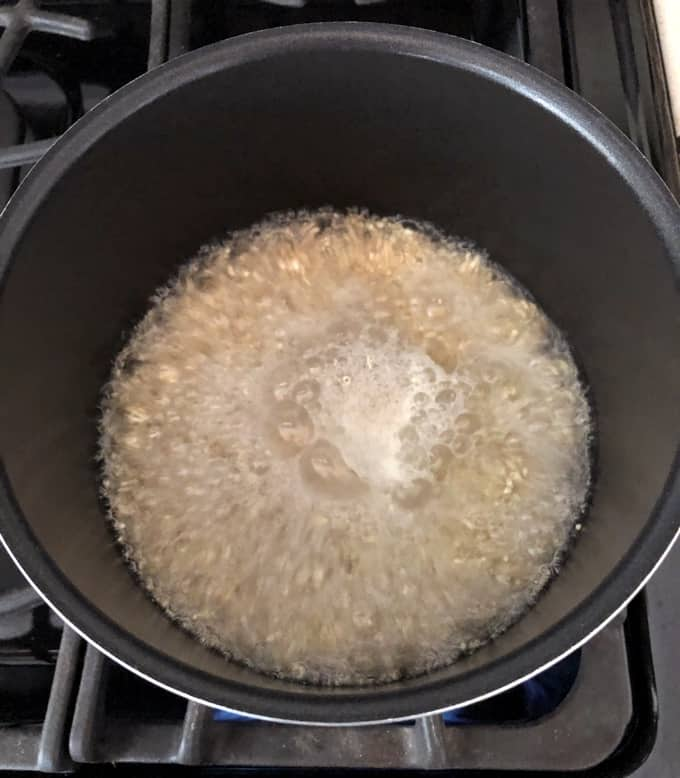 Cooking quinoa in pot at rolling boil.