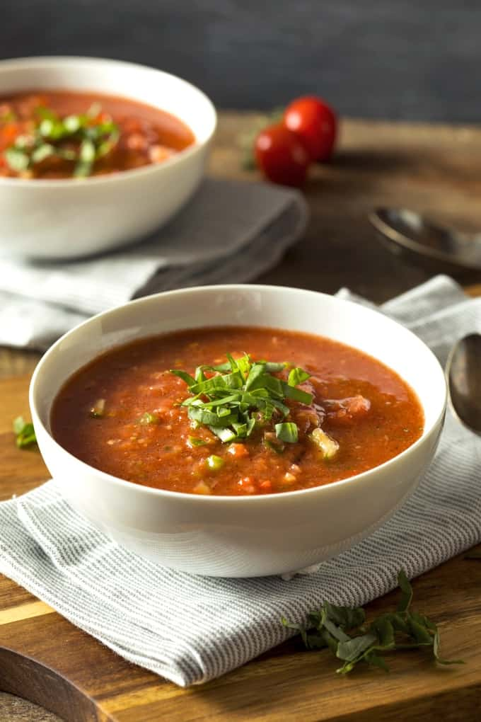Roasted red pepper gazpacho garnished with chopped basil and cucumbers in two white bowls.