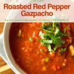 Roasted red pepper gazpacho topped with chopped basil up close.