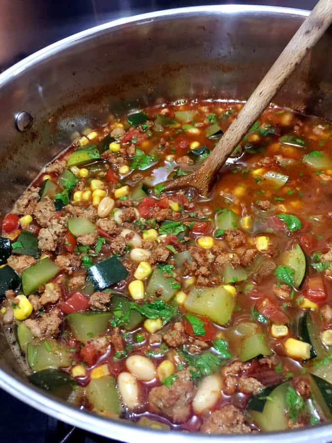Cooking southwestern ground turkey and vegetable soup in large soup pot with wooden spoon.