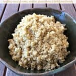 Plain cooked quinoa in green ceramic bowl on wooden table.