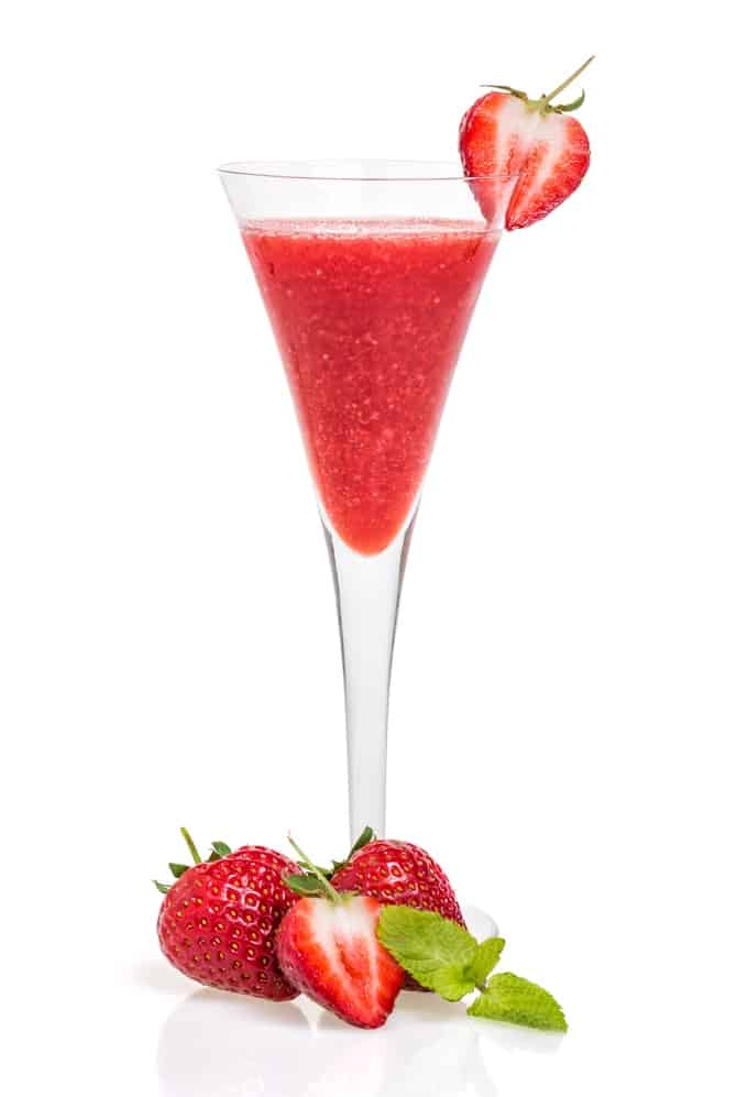 Strawberry cocktail in a champagne flute garnished with fresh strawberries.