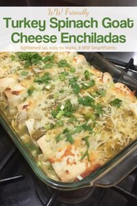 Turkey spinach goat cheese enchiladas verdes in glass baking dish garnished with chopped green onions and cilantro.