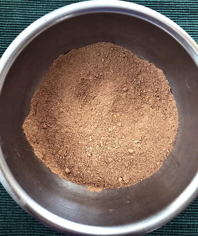 Almond flour mixed with cocoa powder in stainless steel bowl.