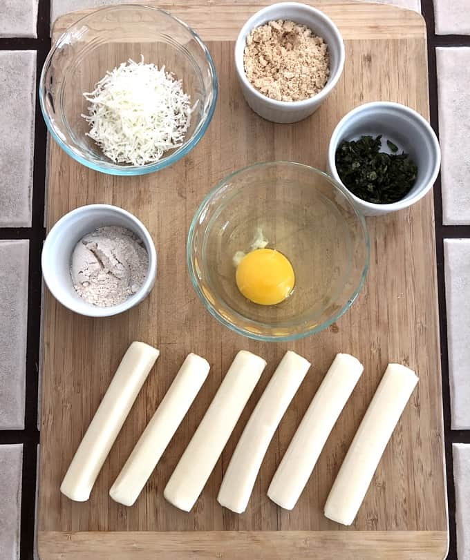 Grated Parmesan, all-purpose flour, cashew flour, chopped basil, egg and six mozzarella cheese sticks on wood cutting board for making baked cheese sticks.