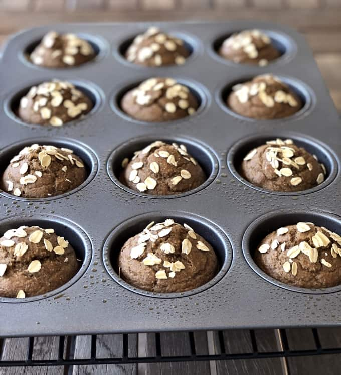 Banana oat muffins cooling in muffin pan on wire rack.