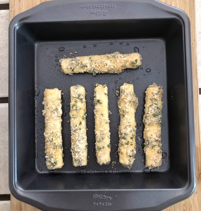 Coated mozzarella cheese sticks in baking pan.