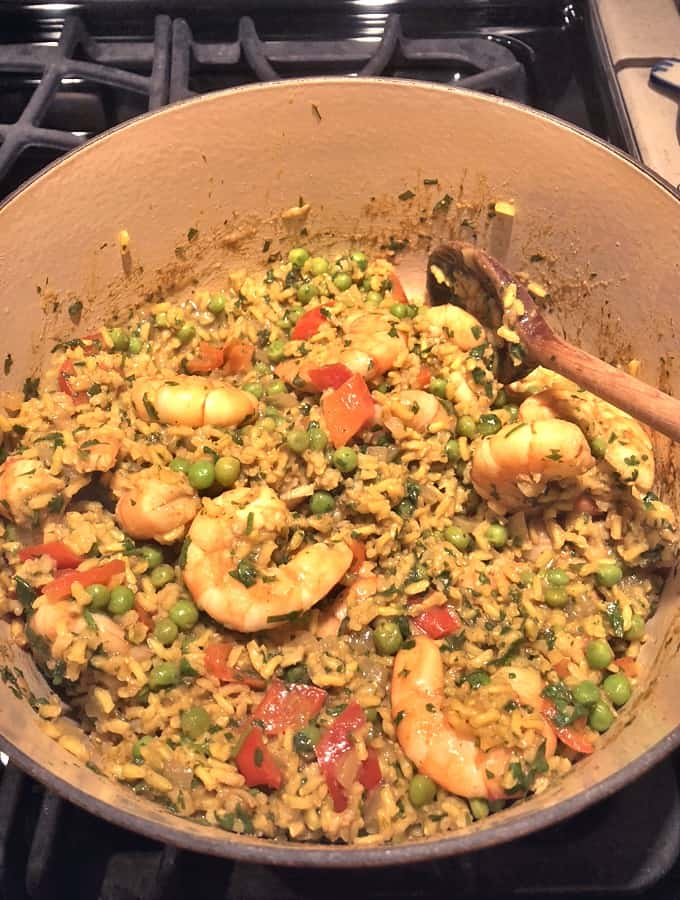 Stirring curried rice and shrimp pilau (pilaf) in skillet with wooden spoon.