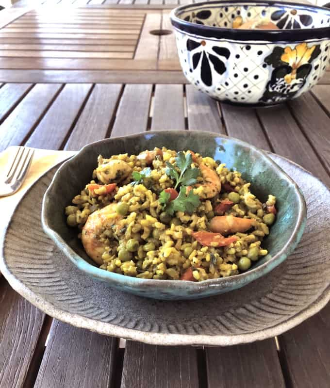 Curried rice and shrimp pilau in green ceramic bowl on wooden table with decorative hand-painted blue and white bowl.