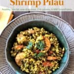 Curried rice shrimp pilau/pilaf in green ceramic dish on wooden table.
