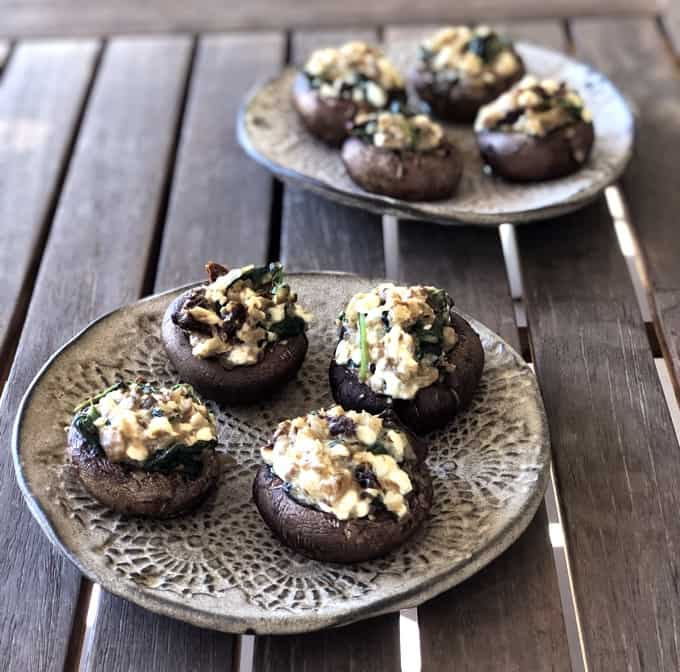 Two plates with vegetarian stuffed mushrooms on wooden table.